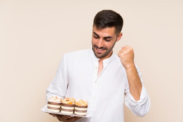 Knappe de muffincake die van de mensenholding een overwinning vieren