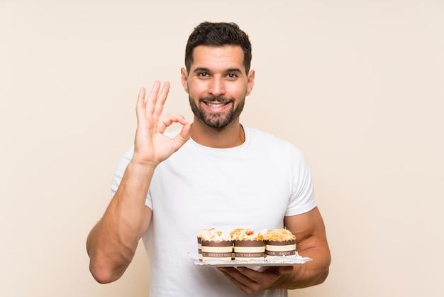Knappe de muffincake die van de mensenholding ok teken met vingers tonen