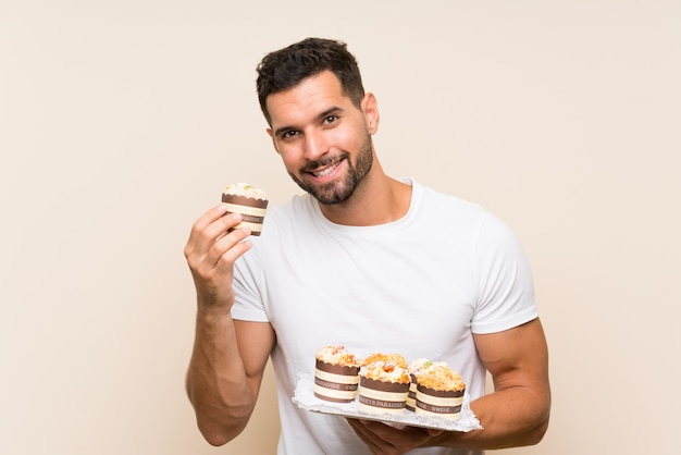 Knappe de muffincake van de mensenholding