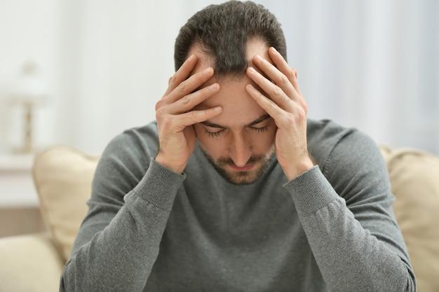 Knappe depressieve man thuis, close-up