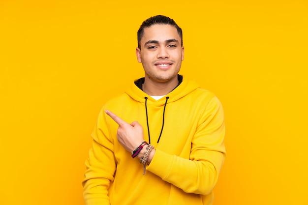 Knappe die mens bij het gele muur groeten met hand met gelukkige uitdrukking wordt geïsoleerd