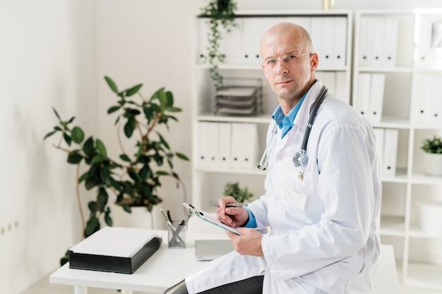 Knappe dokter in whitecoat zittend op een bureau en op zoek naar jou tijdens het maken van medische aantekeningen of recepten