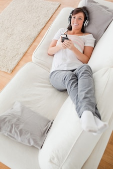 Knappe donkerbruine vrouw op de telefoon terwijl het liggen op een bank