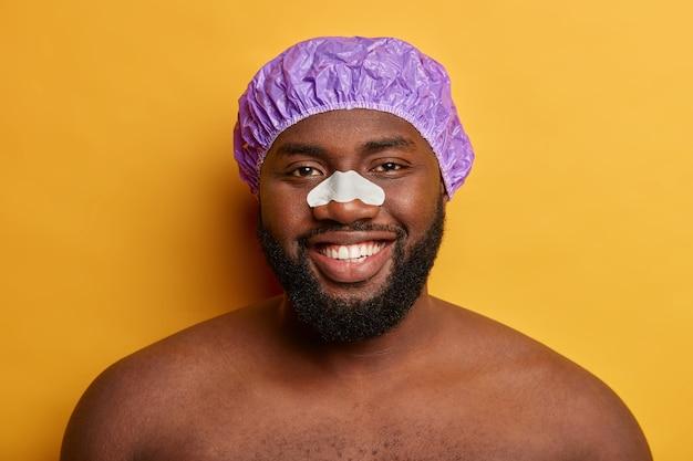 Knappe donkere man gebruikt neuslapje voor het verminderen van zwarte stippen en rimpels, draagt een douchemuts. gezichtsreiniging en verzorgingsconcept