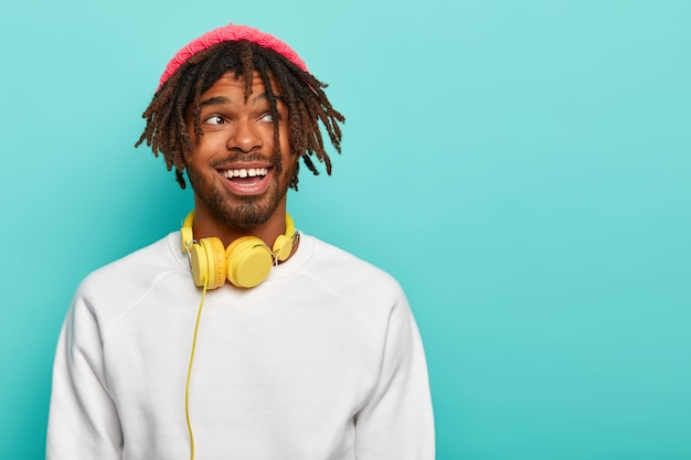 Knappe donkere man met dreadlocks geniet van uitstekend geluid in stereohoofdtelefoons, draagt roze hoed en witte trui