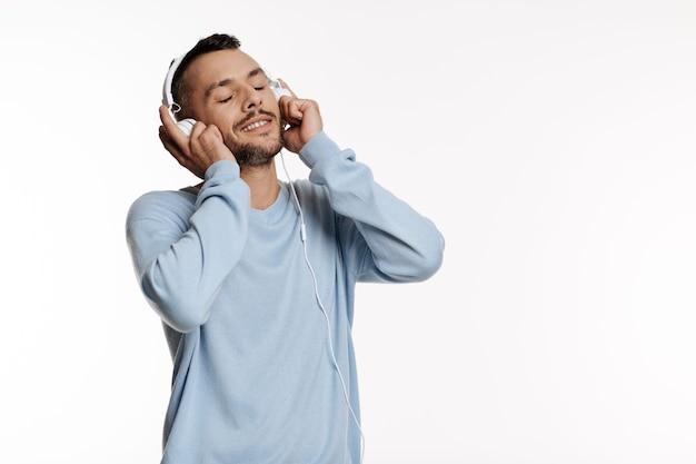 Knappe donkerharige man in een blauwe trui luisteren naar de muziek in de koptelefoon terwijl poseren op wit