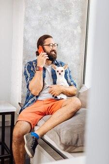 Knappe donkerharige man lacht terwijl hij aan de telefoon spreekt en hond vasthoudt