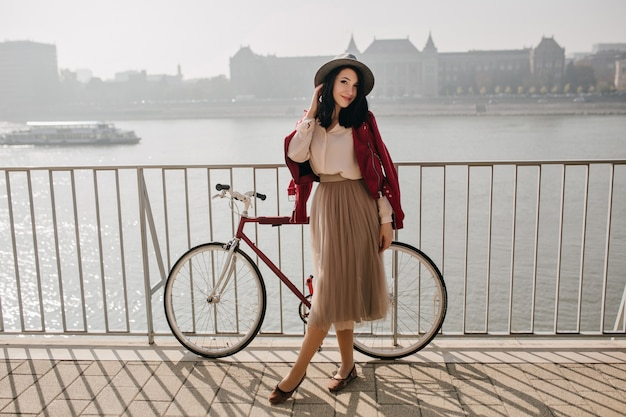 Knappe donkerharige vrouw in rok tijd doorbrengen in de buurt van rivier