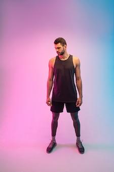 Knappe doordachte bebaarde europese jongeman. vooraanzicht van man slijtage tanktop. geïsoleerd op blauwe en roze achtergrond. studio opname. ruimte kopiëren