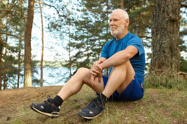 Knappe doordachte oudere man in stijlvolle sportkleding, zittend op de grond onder een dennenboom, met een ontspannen gezichtsuitdrukking, overweegt de prachtige natuur om hem heen na het hardlopen van de training