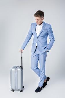 Knappe elegante jonge man in blauw pak permanent met koffer