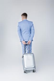 Knappe elegante jonge man in blauw pak staat met zijn rug met koffer