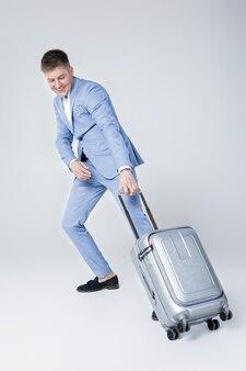 Knappe elegante jonge man in blauw pak wandelen met koffer
