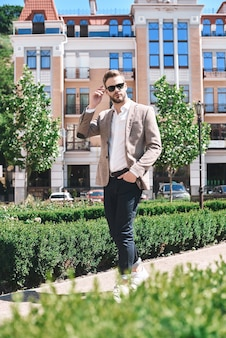 Knappe elegante jonge man in stedelijke omgeving in europese stad wandelen