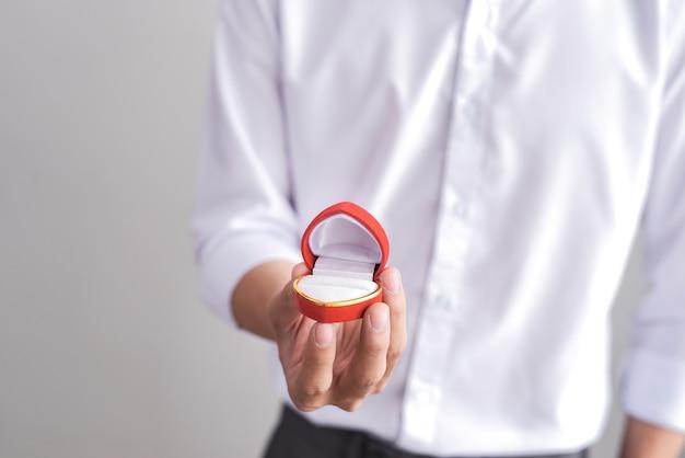 Knappe elegante man in een wit overhemd houdt een doos met een verlovingsring vast en toont in de camera.