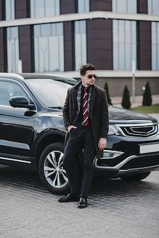 Knappe elegante man in zakelijke slijtage staande in de buurt van zijn moderne auto