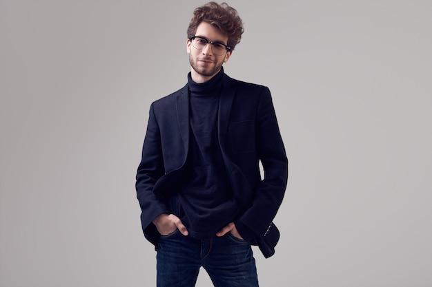 Knappe elegante man met krullend haar dragen pak en bril