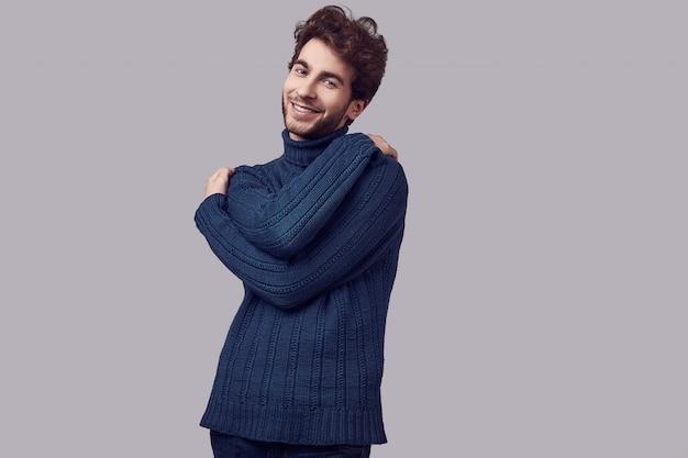 Knappe elegante man met krullend haar in blauwe trui
