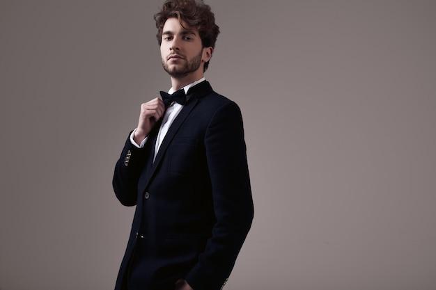 Knappe elegante man met krullend haar smoking dragen