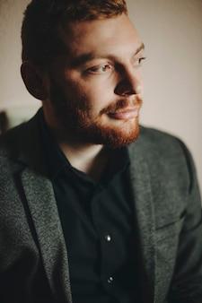 Knappe elegante man met rode baard grijnzend en wegkijken terwijl hij op een grijze achtergrond