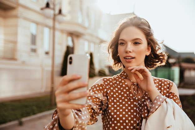 Knappe elegante vrouw met smartphone en selfie maken. geweldige europese dame in bruine jurk die zich voordeed op straat.