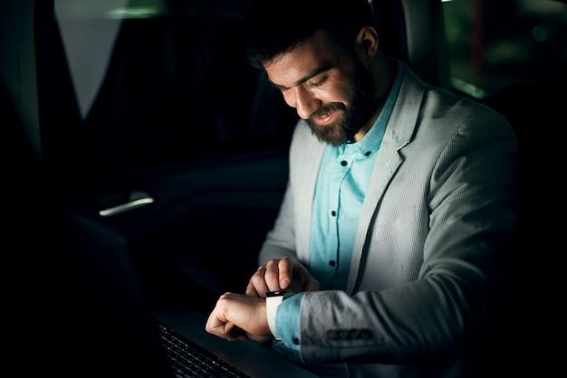 Knappe elegante zakenman kijkt 's nachts naar het horloge op de achterbank van een auto.
