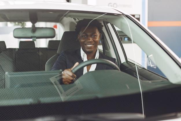 Knappe en elegante man in een autosalon