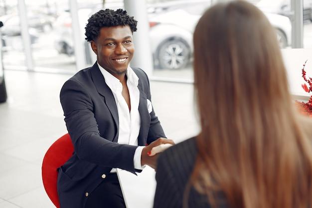 Knappe en elegante zwarte man in een auto salon