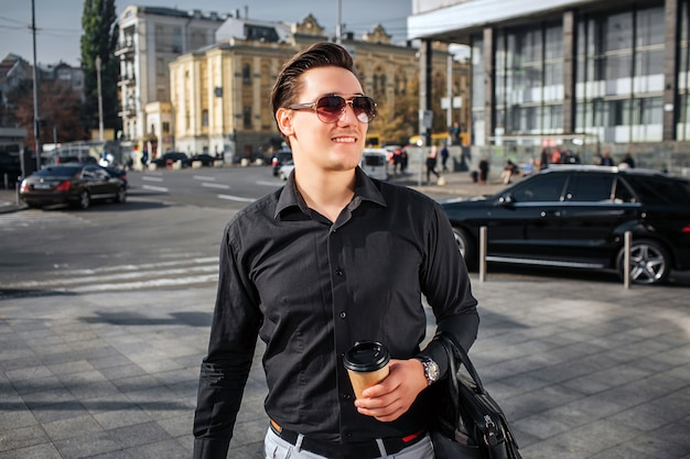 Knappe en gelukkige jonge man loopt op straat. hij kijkt naar rechts door een zonnebril. jonge man heeft kopje drank en lederen tas. hij is zelfverzekerd.