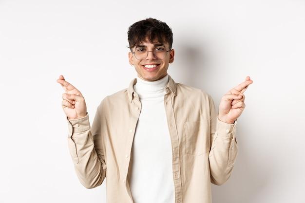 Knappe en positieve jonge man die lacht, wens doet met gekruiste vingers en blij gezicht, hoop dat een droom uitkomt, staande op een witte muur.