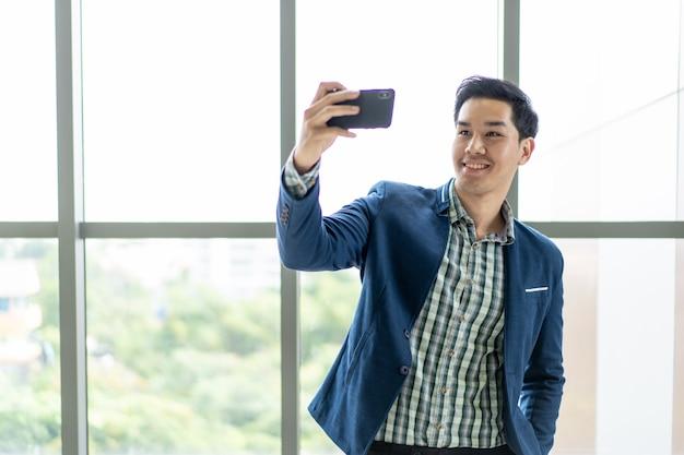 Knappe en slimme aziatische zakenman die selfie foto, gelukkige bedrijfsmensen en werkplaats spreken.