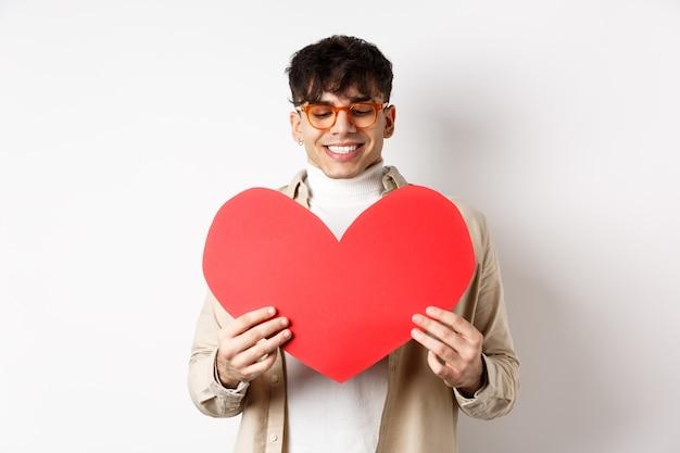 Knappe en stijlvolle man in zonnebril, bereid verrassingsbriefkaart voor vriendin op valentijnsdag, met groot rood hart knipsel en glimlachend blij, staande op witte achtergrond.