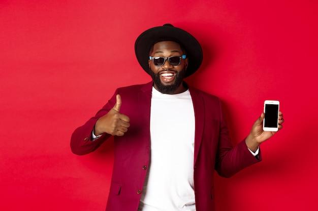 Knappe en stijlvolle zwarte man die het telefoonscherm en de duim naar de camera laat zien en de online winkel-app aanbeveelt, rode achtergrond
