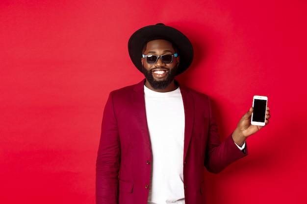 Knappe en stijlvolle zwarte man met telefoonscherm