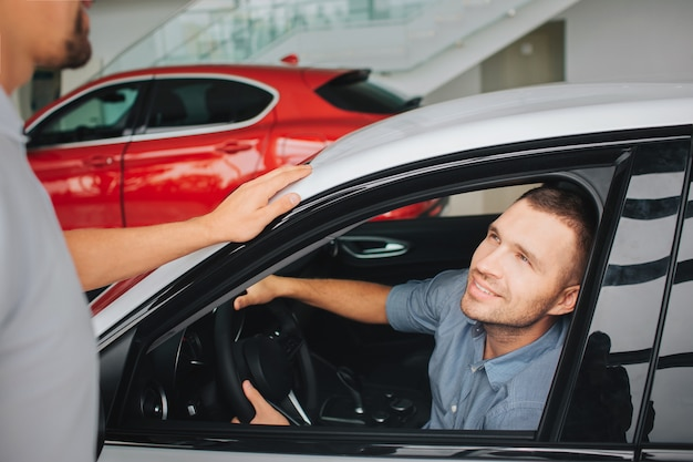 Knappe en tevreden jonge mannen zitten in witte auto en kijken naar manager. hij lacht. man hand in hand op het stuur. bebaarde manager staat naast witte auto en kijk naar de klant.