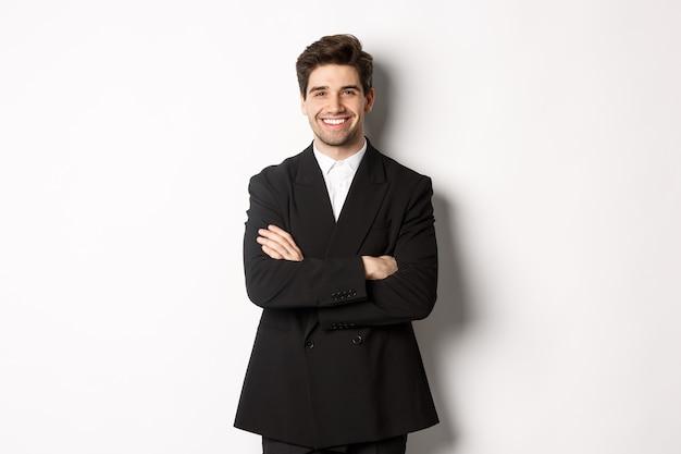 Knappe en zelfverzekerde bebaarde man, staande in een formeel pak met de handen gekruist op de borst, tevreden glimlachen, een feest of werkevenement bijwonen, staande op een witte achtergrond.