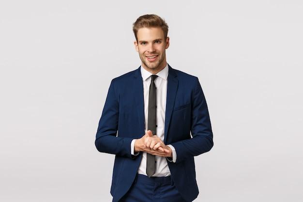 Knappe en zelfverzekerde, slimme mannelijke ondernemer in klassiek pak, handpalmen wrijvend en glimlachend tevreden, anticiperen om veel geld te verdienen, goede deal, genieten van iets goeds