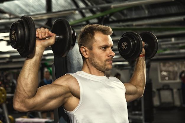 Knappe ernstige geschiktheidsmens die gewichtheffenoefeningen met domoren doen bij de gymnastiek