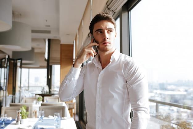 Knappe ernstige jonge man praten via de mobiele telefoon.