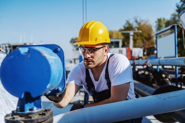 Knappe ernstige kaukasische werkman in overall en met helm op hoofd dringende knoop op dashboard terwijl het buigen op tanker.