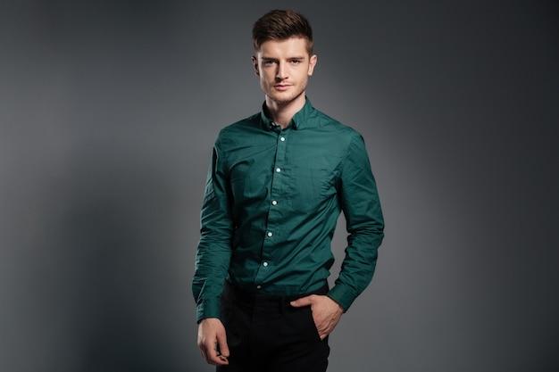 Knappe ernstige man gekleed in shirt poseren