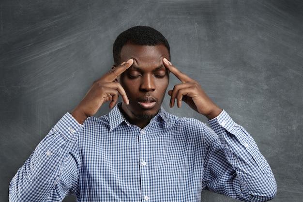 Knappe ernstige verbaasde afrikaanse student gekleed in geruit overhemd zijn voorhoofd beroven, zijn ogen sluiten, geconcentreerd en gefocust kijken, proberen het juiste antwoord te onthouden tijdens de test in de klas