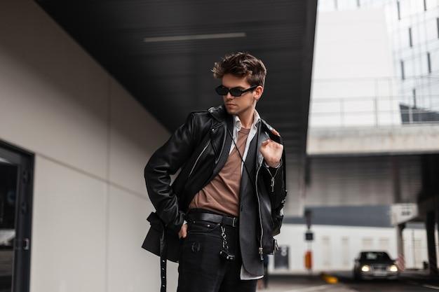 Knappe europese jongeman in oversized modekleding voor jongeren met een trendy kapsel rust op een lentedag in de buurt van een modern gebouw in de stad. moderne kerel hipster in stijlvolle zonnebril buitenshuis.