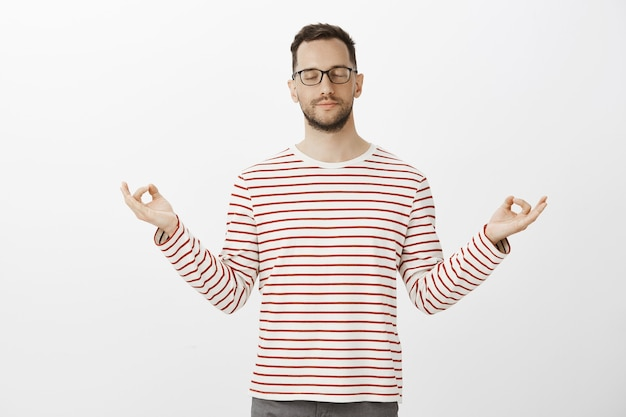 Knappe europese kerel die yoga beoefent, trendy outfit en bril draagt, handen spreidt in zen-gebaar en mediteert met gesloten ogen en lichte glimlach, zich kalm voelt over grijze muur
