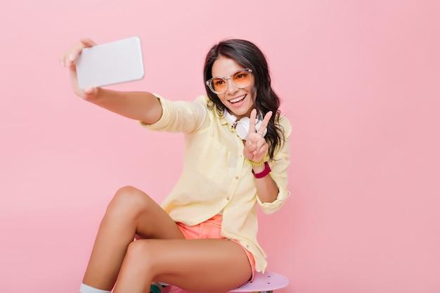 Knappe europese vrouw met bronzen kleurtje selfie maken op smartphone. blij lief meisje in geel jasje dat foto van zichzelf met vredesteken neemt.