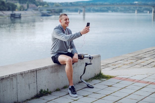 Knappe fit sportieve kaukasische gehandicapte man in sportkleding en met kunstbeen zittend op de kade en bericht aan het typen op slimme telefoon.