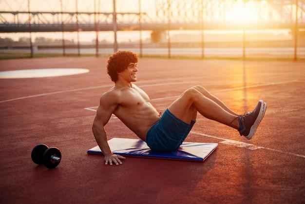 Knappe fit yong man doet crunches op een trainingsveld buiten. ochtendtraining in de vroege zomer.