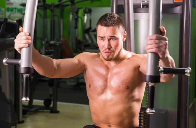 Knappe fitness man werkt in de sportschool