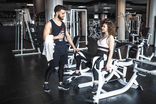 Knappe fitnessinstructeur helpt zijn aantrekkelijke klant om te trainen op een oefening in de sportschool