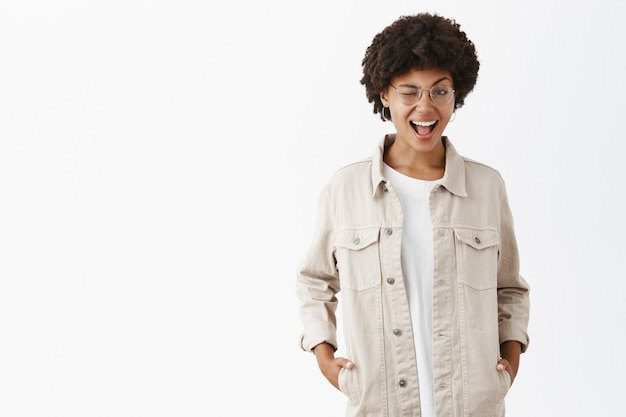 Knappe flirterige zelfverzekerde lesbische tomboy met een donkere huidskleur in een bril en beige overhemd, knipoogt, hand in hand in zakken en lachend met gewaagde uitdrukking